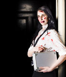 Dead female zombie worker holding briefcase Royalty Free Stock Images