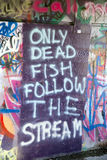 Only Dead Fish Follow the Stream - Wall Graffiti Royalty Free Stock Image