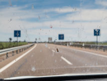 Dead insects on windscreen windshield. Splattering of dead insects on a car windscreen, windshield whilst driving along a road with signs and road white markings royalty free stock photo