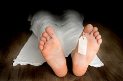 Dead man lying on the floor under white cloth Royalty Free Stock Photo