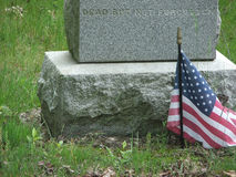 Dead But Not Forgotten. Grave marker of a Civil war veteran engraved with the sentiment 'Dead But Not Forgotten' with a small American flag in the foreground stock photo