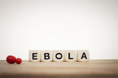 Dead pawn next to word Ebola spelled by toy dice Stock Images