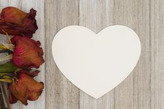 Dead red roses with heart-shape card on weathered wood backgroun Stock Images