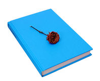 Dead rose on hardcover blue book Stock Photo