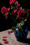 Dead roses. On the wood table in the dark Stock Photos