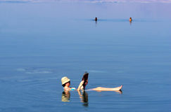 Dead Sea. A young woman floating while reading a magazine at the Dead Sea, Israel Royalty Free Stock Photos