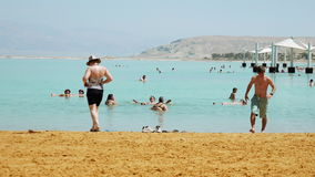 Dead sea beach panoramic shot. Dead Sea, Israel - May 22, 2017: Dead sea beach panoramic shot. People are bathing and swimming in the most salty sea on the stock video