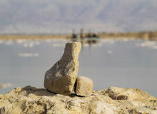 At the Dead Sea. Focusing on a rock while behind lays an old salt harvest rig Royalty Free Stock Photos