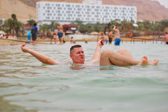 Dead sea in Israel. A man on the water of the dead sea in Israel. Man floating in a glassy water of dead sea royalty free stock photos