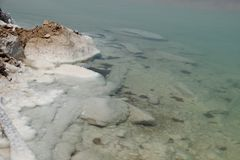 The stones overgrown with white salt on a dead sea and blue green transparent water royalty free stock photos
