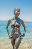 Dead sea mud body care treatment jordan. One caucasian woman applying dead sea mud body care treatment  in jordan Stock Photo