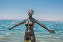 Dead Sea mud body care treatment Jordan. One  woman applying Dead Sea mud body care treatment in Jordan Stock Images