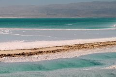 The Dead Sea. Salty water and salt forms, texture and transparency of the Dead Sea and Jordan mountains, Israel Stock Images