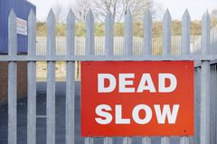 Dead slow road safety sign on industrial business park fence. Uk royalty free stock image