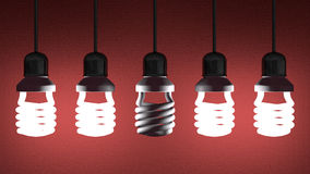 Dead spiral light bulb hanging among glowing ones Royalty Free Stock Photo