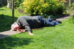 Dead or unconscious elderly man lying down. An elderly man lying down on a garden path either dead or unconscious. A walking stick lies by his side stock photography