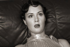Dead woman lying on the sofa. Studio shot. Strangled beautiful young woman. Studio shot in a retro style Royalty Free Stock Images