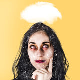 Dead zombie business woman brainstorming a idea. Stressed undead businesswoman under cloud of chaos and turmoil brainstorming a way out of the haze and confusion Stock Photos