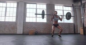 Deadlift praticando do atleta fêmea com barra do peso filme
