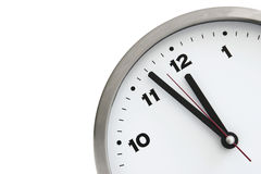 Deadline. 11:57 on the white wall clocks (isolated stock image