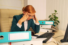 Deadline concept. Businesswoman overworking and feeling headache Royalty Free Stock Image