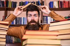 Deadline concept. Teacher or student with beard sits at table making roof out of book, defocused. Man on shocked face. Between piles of books, while studying in Royalty Free Stock Photography