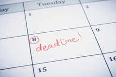 Deadline date writting on timeline planner. Closeup planner calendar, blurred at the edges. Focus on the red word Deadline written on timetable with circle stock image