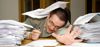 Deadline with paperwork. Desperate businessman reaching for help with paperwork - cocnept for overtime, deadlines and stress Royalty Free Stock Photography