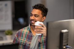 Happy creative man drinking coffee at night office. Deadline and people concept - smiling creative man working and drinking coffee at night office stock photos