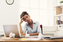 Frustrated business woman with headache at office. Deadline stress concept - sad african-american business woman sitting at desktop in office and holding hand on Royalty Free Stock Photos