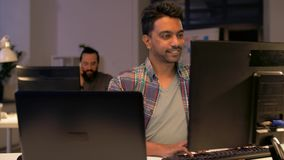 Creative man with laptop working at night office stock video footage