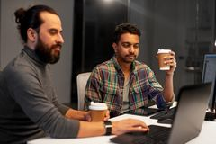 Creative team drinking coffee at night office Stock Photography