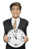 Deadline for a yuppie. Young Indian businessman, yuppie type, stressed with a desperate and pressured grin on his face, holding a clock pointing five to twelve Stock Images