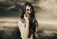 Chill of death in mourning. Deadly blizzard of falling snow pouring down on a dead female zombie crying tears of pain Stock Photography