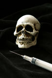 Deadly Dose of Death. Head of death overlooking a syringe on black Stock Images