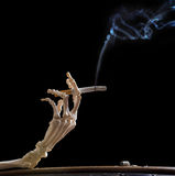 Deadly hand. Hand of death holding a smoking cigarette Stock Images