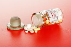 Deadly pills spilled out of glass chemical bottle. Poisonous chemical pills spilled out of vintage labeled chemical bottle with skull Royalty Free Stock Photo