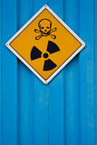 Deadly radiation warning sign. Deadly nuclear radiation warning sign with skull and crossbones on blue background Royalty Free Stock Photo