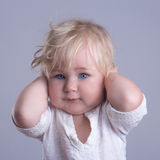 Deaf baby blue eyes blonde. Long hair gray background royalty free stock photography