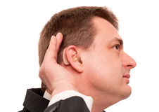 Deaf Business Man. Deaf man wearing hearing aid listening for a quiet sound. Isolated on white Royalty Free Stock Photography
