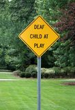 Deaf child at play sign. In a neighborhood stock photography