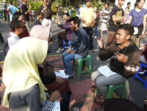Deaf. Citizens interact with deaf persons in a public space in the city of Solo, Central Java, Indonesia stock photo