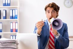 The deaf employee using hearing aid in office. Deaf employee using hearing aid in office stock image