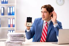 The deaf employee using hearing aid in office. Deaf employee using hearing aid in office stock photo