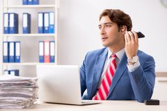 The deaf employee using hearing aid in office. Deaf employee using hearing aid in office stock images