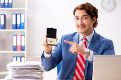 The deaf employee using hearing aid in office. Deaf employee using hearing aid in office royalty free stock photo