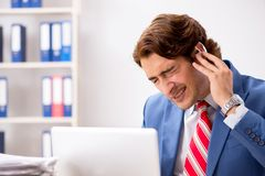 The deaf employee using hearing aid in office. Deaf employee using hearing aid in office stock photography