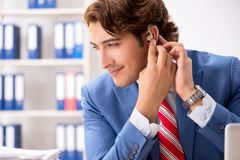 The deaf employee using hearing aid in office. Deaf employee using hearing aid in office royalty free stock photography