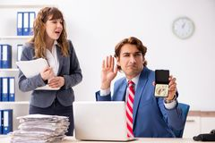 The deaf employee using hearing aid talking to boss. Deaf employee using hearing aid talking to boss stock photo