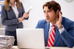 The deaf employee using hearing aid talking to boss. Deaf employee using hearing aid talking to boss stock images